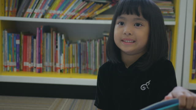 asian girl reading book in library - primary school child stock videos & royalty-free footage