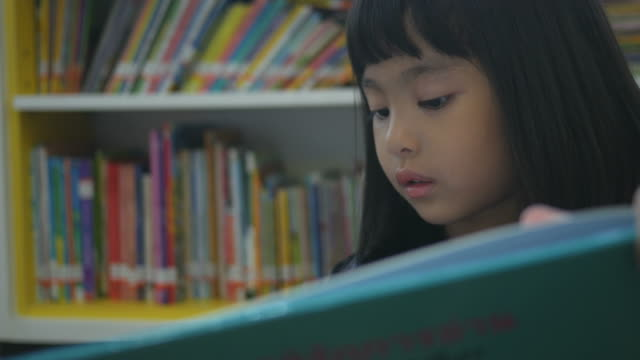 Asian girl reading book in library