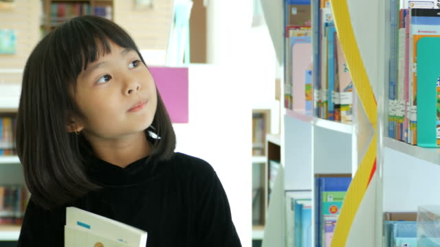 asian girl reading book in library - spelling stock videos & royalty-free footage