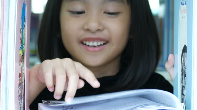 asian girl reading book in library - alertness stock videos and b-roll footage