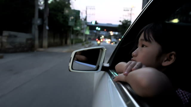 asian girl riding in the car sitting in the car seat and looking out the window. slow motion. - belt stock videos & royalty-free footage