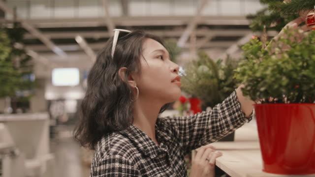vidéos et rushes de asiat shopping pour les décorations de noël dans la boutique de cadeaux. - un seul objet
