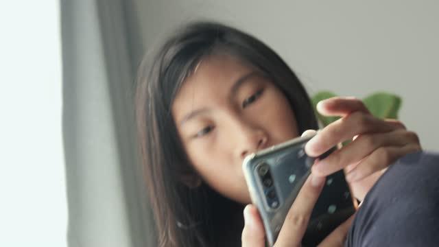 vídeos y material grabado en eventos de stock de chica asiática sentada en la silla con la luz de la ventana y usando el teléfono inteligente en la mañana en casa, concepto de estilo de vida. - nativo digital