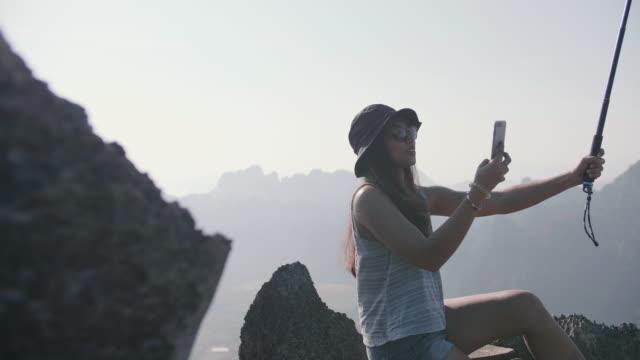 山の頂上に座っているアジアの少女は、自分撮りスティックで自分撮りを取ります。 - 自画像点の映像素材/bロール