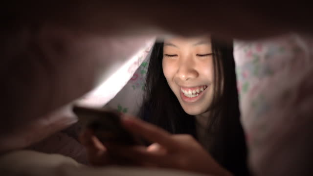 asian girl smiling when texting with her friend in smartphone at night under blanket in bedroom - using digital tablet stock videos & royalty-free footage