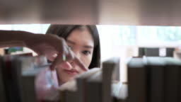 Asian girl student finding and searching book in library of a University.  Education concept.