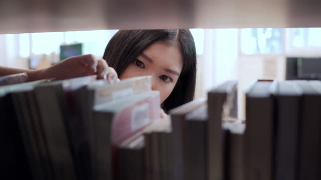 asian girl student finding and taking book in library of a university.  education concept. - bookstore stock videos & royalty-free footage