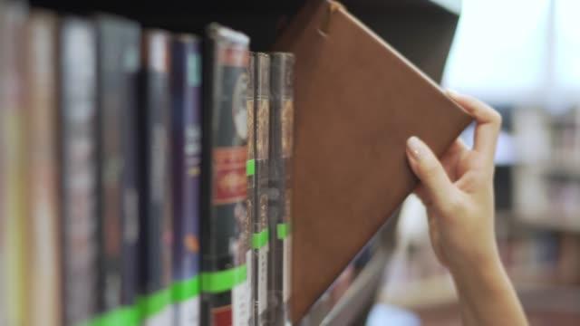 アジアの女の子学生発見し、大学の図書館で本を取って. 教育の概念。 - absence点の映像素材/bロール