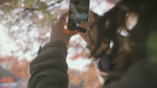 vídeos de stock e filmes b-roll de asian girl take a photo. - fotografando