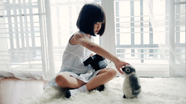 asian girl taking a picture with an old camera against in the living room and a penguin doll for a creativity or vision concept. - teddy bear stock videos & royalty-free footage