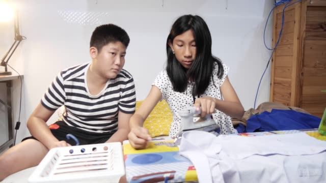 ragazza asiatica che insegna a suo fratello per stirare i loro vestiti di notte, concetto di stile di vita. - asse da stiro video stock e b–roll