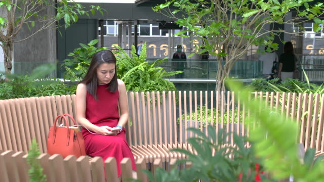 vidéos et rushes de message asiatique de dactylographie de fille sur le smartphone dans le parc vert - robe rouge