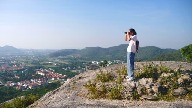 朝は青空、アウトドア冒険コンセプトで山頂に双眼鏡を使用したアジアの女の子。 - 双眼鏡点の映像素材/bロール