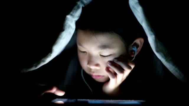stockvideo's en b-roll-footage met asian girl using digital tablet at night - in ear koptelefoon