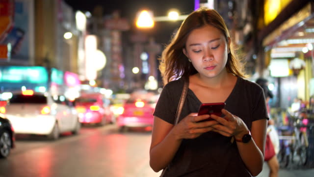 Asian Girl using Mobile Phone During Walk on Streets of Night Town