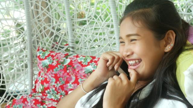 vídeos de stock e filmes b-roll de asian girl using phone - equipamento de parque infantil