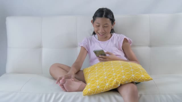 asian girl using smartphone for watching movie or playing game while sitting on sofa at home, lifestyle concept. - digital native stock videos & royalty-free footage