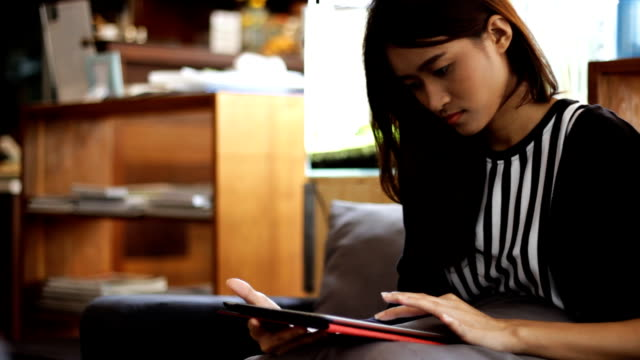 asian girl using tablet to work and study in cafe