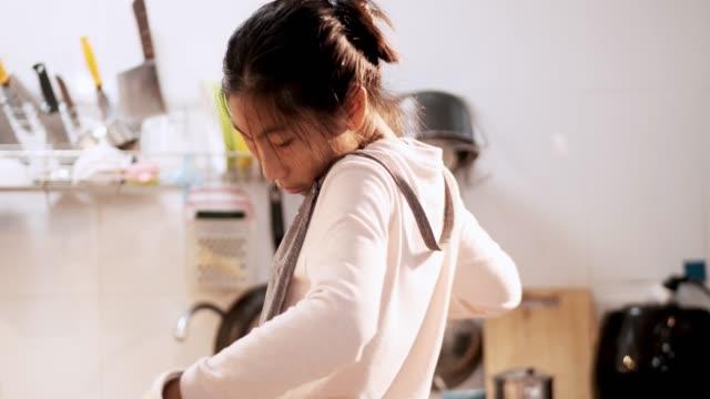 vídeos y material grabado en eventos de stock de chica asiática que lleva delantal antes de cocinar papas fritas por sí misma en casa, concepto de estilo de vida. - delantal