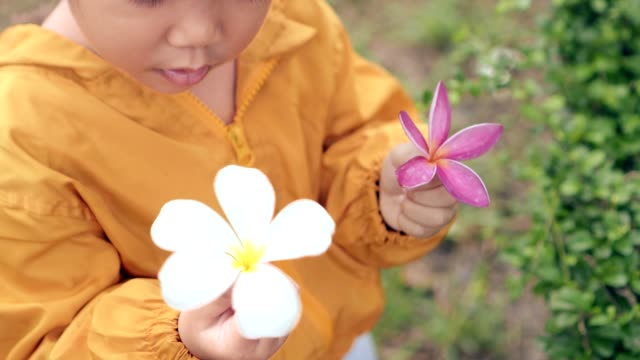 asian girl-child hold flower and spinning