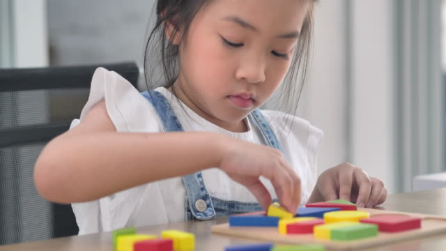 asian girls age 6-7 years kids playing with colorful wooden toy blocks staying home.homeschooling and distance learning - 6 7 years stock videos & royalty-free footage