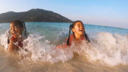 Asian girls are having fun with sea waves while they are lie on the beach
