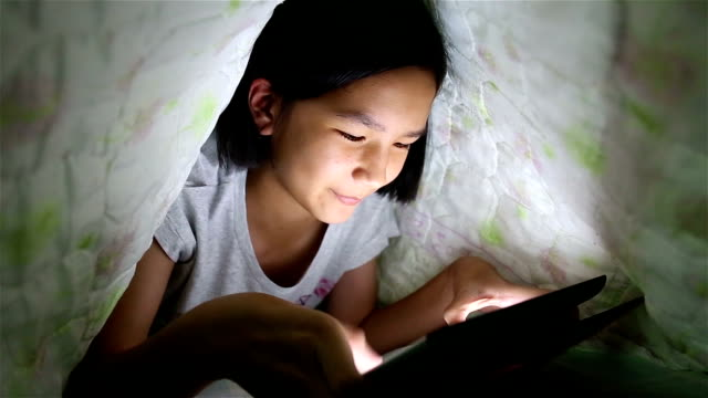 Asian girls play on tablet on the bed.