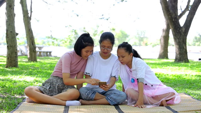 asian girls playing games on tablet in garden.happy family concept. - template stock videos and b-roll footage