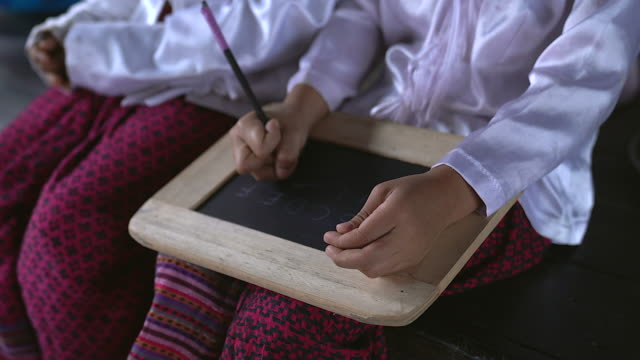 asian girls writing the alphabet in a chalkboard and showing children writing on slate board.poverty children using the slate chalkboard to learning alphabet. - village stock videos and b-roll footage