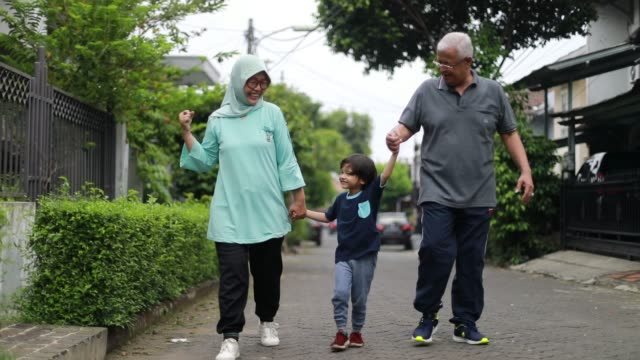 asian grand parent walking with their grandchild on the street - indonesia stock videos & royalty-free footage