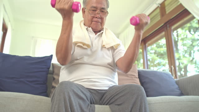 asian grandfather lifting small weihgt at home for exercise in living room.healthly concept. - sweat stock videos & royalty-free footage