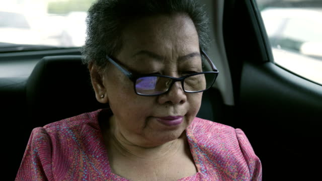 アジアのおばあちゃんと車にデジタル タブレット - passenger点の映像素材/bロール
