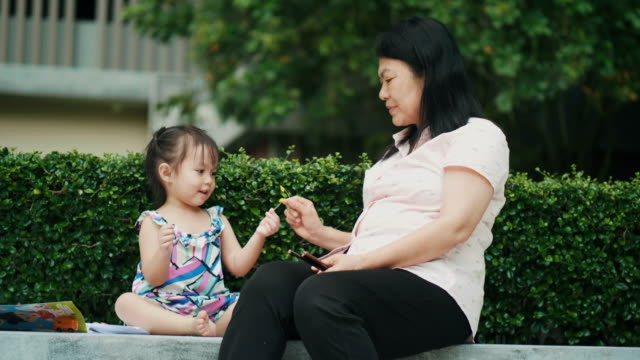 Asian grandmother and niece are play of flower at the garden-modern lifestyles of Thai