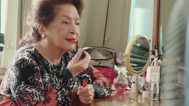 vidéos et rushes de grand-mère asiatique application maquillage - miroir ancien
