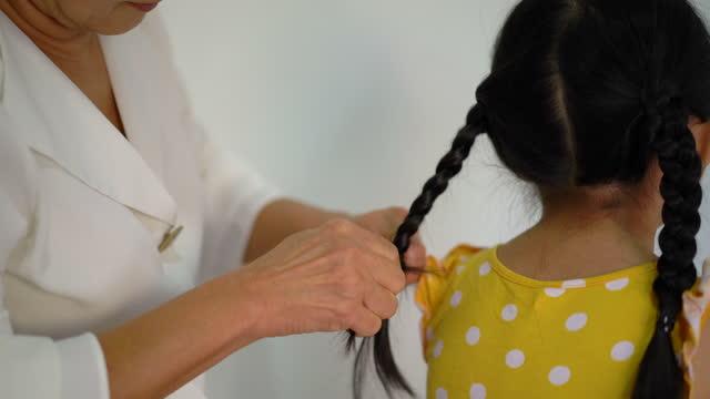彼女の孫娘の髪をしているアジアの祖母 - 編み込みヘア点の映像素材/bロール
