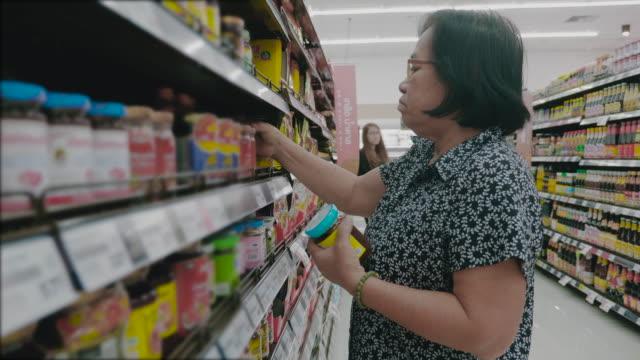 vídeos de stock e filmes b-roll de asian grandmother in grocery store - etiqueta mensagem