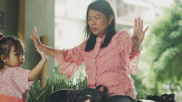 asian grandmother is flying and imitation of bird while teaching her granddaughter with positive emotion - 60 64 years stock videos & royalty-free footage