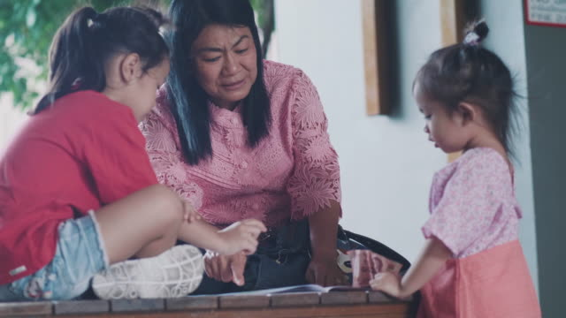 asian grandmother is reading book for teaching her niece to imagine and thinking together - storytelling stock videos & royalty-free footage