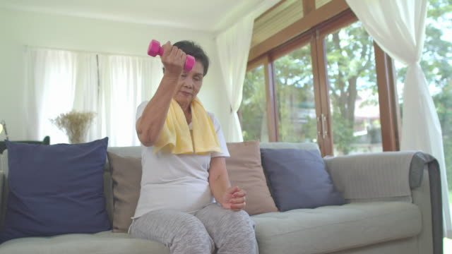 asian grandmother lifting small weihgt at home for exercise in living room.healthly concept. - exercise room stock videos & royalty-free footage