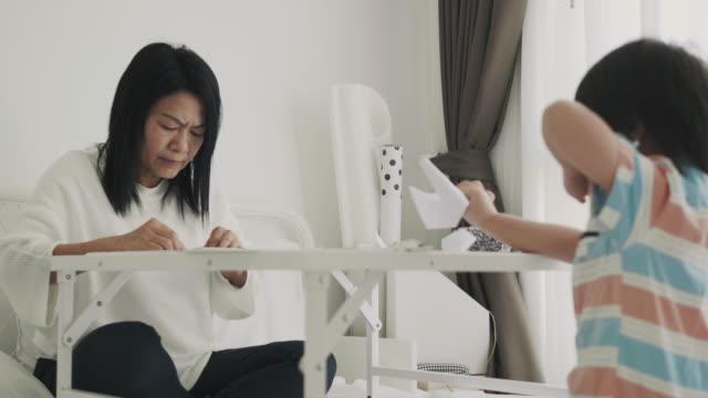 彼女の部屋の diy 製品を持つ鳥の折り紙を行う孫を教えるアジアの祖母 - 東洋民族点の映像素材/bロール