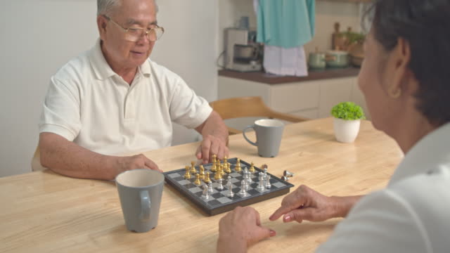 asian grandparent playing chess with enjoy in kitchen room table ,activity for leisure, lifestyle concept. - game night leisure activity stock videos & royalty-free footage