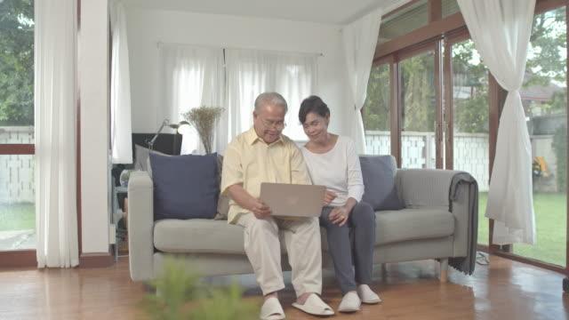 vídeos de stock, filmes e b-roll de os avós asiáticos ficam em casa por causa do covid-19 usando laptop e celular para conversar com a família na sala de estar. - idoso na internet
