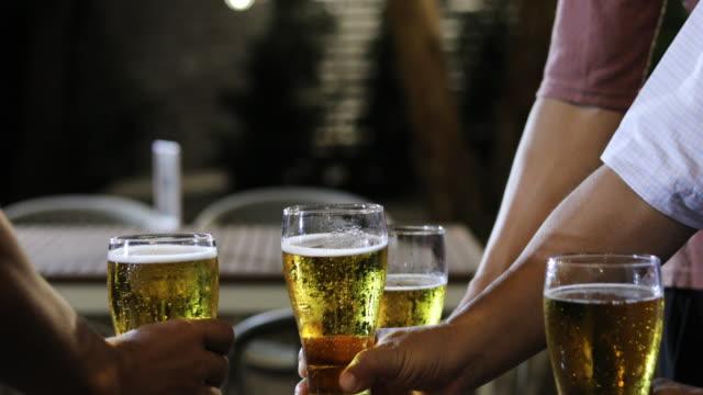 アジアの友人グループがアルコールビールを飲みながらパーティーを開き、若者たちはバーでカクテルを乾杯し、眼鏡をかけて楽しんでいます - 乾杯点の映像素材/bロール