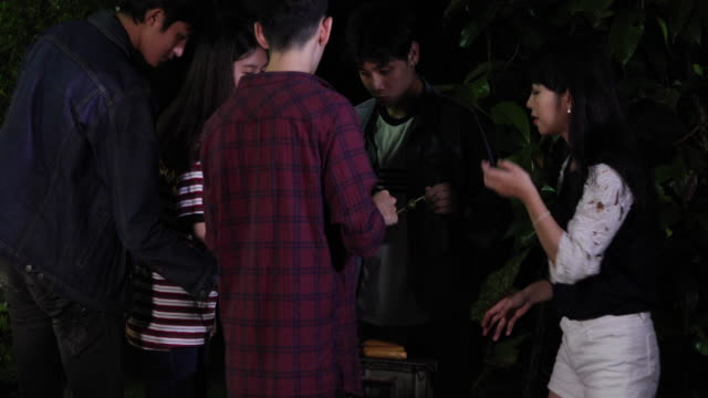 Asian group of Friends making barbecue and grilled shashliks on grate party in outdoor garden
