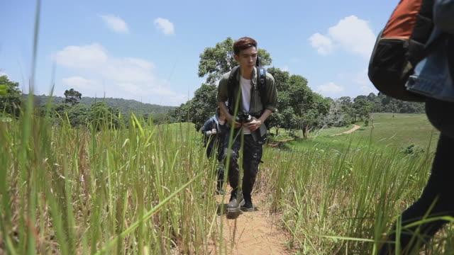asiatiska grupp unga människor vandra med vänner ryggsäckar gå tillsammans och letar karta och ta foto kamera vid vägen och ser lycklig, slappna av tid på semesterkoncept resor - gå tillsammans bildbanksvideor och videomaterial från bakom kulisserna
