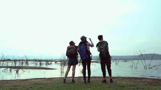 アジアの若者グループ は、一緒に歩いて、地図を見て、道路で写真カメラを撮って、休日のコンセプト旅行で時間をリラックスして友人のバックパックとハイキング - 双眼鏡点の映像素材/bロール