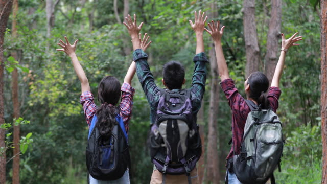 asian group of young people hiking with friends backpacks walking together and looking map and taking photo camera by the road and looking happy ,relax time on holiday concept travel - zaino da montagna video stock e b–roll