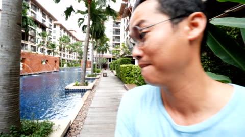 asiatisk kille tar en selfie video blog vid poolen. - digital spegelreflexkamera bildbanksvideor och videomaterial från bakom kulisserna