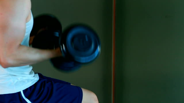 Asian handsome man is playing dumbbell at home-fitness lifestyle