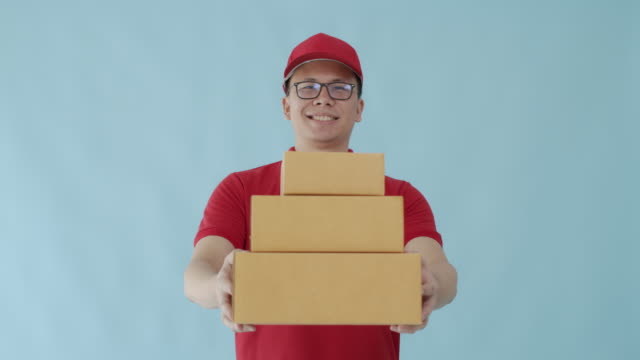 asian happy delivery man carrying paper parcel boxes isolated on blue colour background with smiling face.concept of postal delivery service. - isolated colour stock videos & royalty-free footage